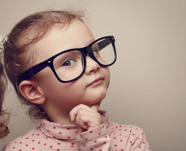 Thinking kid girl in glasses looking happy. Closeup